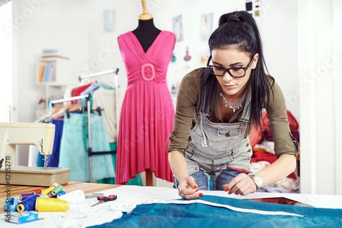 Fotografija  Young female designer measuring textile material
