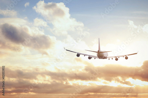 airplane in sunset sky Canvas Print