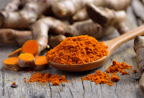 Photo  pile of fresh turmeric roots on wooden table