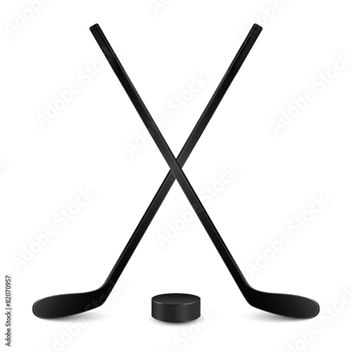 Two crossed hockey sticks and puck. Isolated on white Poster