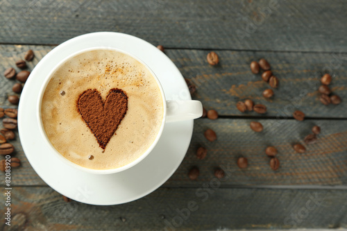 Fototapeta Cup of cappuccino with heart of cocoa on wooden table obraz