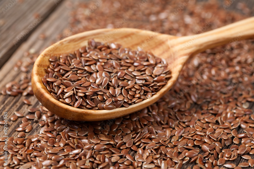 Fototapety, obrazy: Heap of flax seeds in vintage wooden spoon