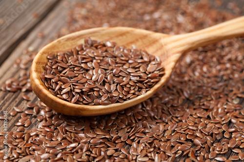 Obraz Heap of flax seeds in vintage wooden spoon - fototapety do salonu