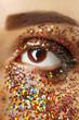 Female eye with fancy glitter makeup, macro view