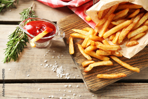 Tablou Canvas Tasty french fries on cutting board, on wooden table background