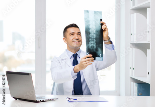 Fotografía  smiling male doctor in white coat looking at x-ray
