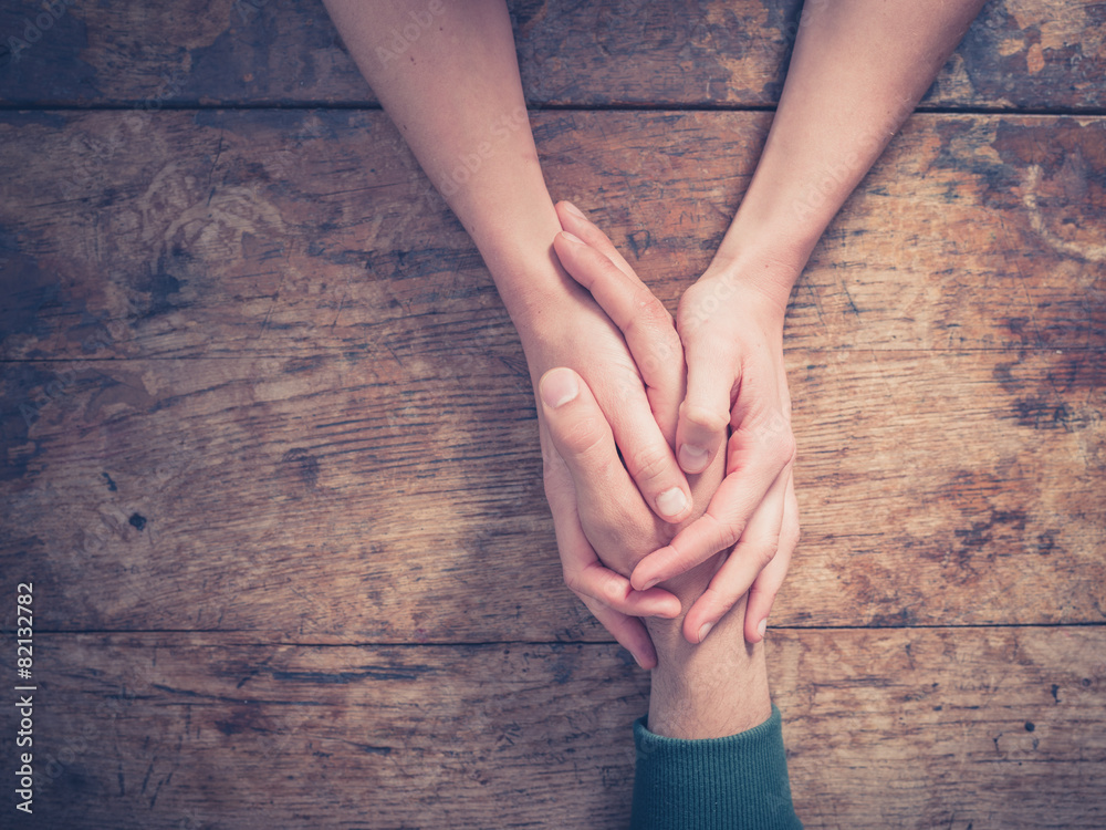 Fototapeta Man and woman holding hands at a table