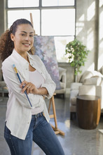 Dominican Woman Holding Paintbrush In Living Room