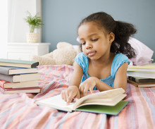 Mixed Race Girl Reading Book In Bedroom