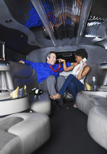Multi-ethnic Couple In With Champagne And Money In Limousine
