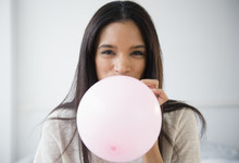 Mixed Race Woman Blowing Up Balloon