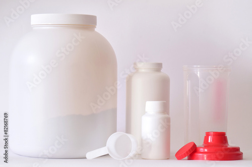 Fotografia  Big jar of protein powder, bottles and shaker