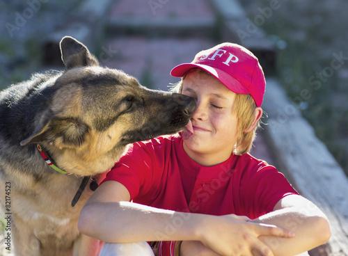 Dog licking Caucasian boy's face