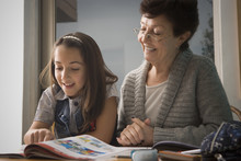 Older Hispanic Woman Reading With Granddaughter