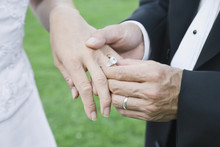 Asian Groom Putting Ring On Bride's Finger