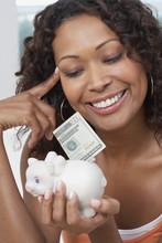 African Woman Putting Money In Piggyback