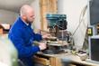 Man working on a machine at guitar workshop