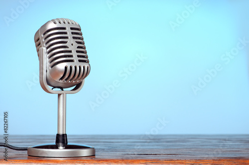 Fotografía  Vintage microphone on the table with cyanic background