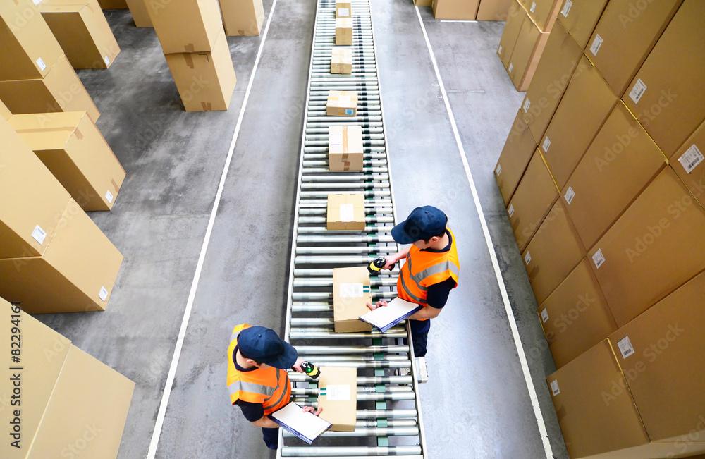 Fototapeta Pakete und arbeiter im Warenversand eines Onlinehandels