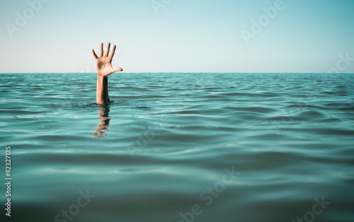 Hand in sea water asking for help. Failure and rescue concept. Fotobehang