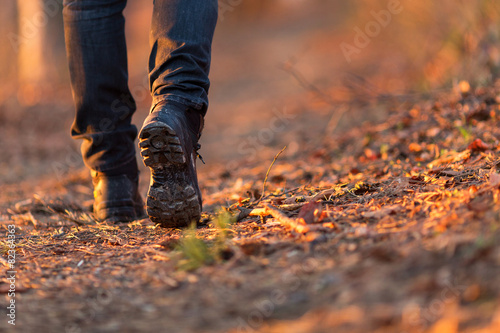 Fototapeta Closeup of woman legs hiking in nature at sunset. obraz