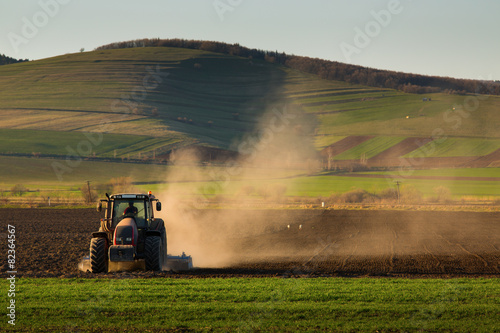 Tractor in sunset plowing the field Obraz na płótnie