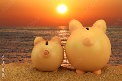 Obraz na plátne Two piggy banks on the beach looking to the sunset