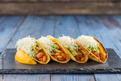 Fotografie, Obraz  Mexican tacos with meat, beans, avocado, cheese and tomato sauce