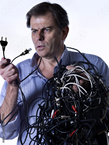 Fotografie, Obraz  Man tangled in power cables, looking puzzled