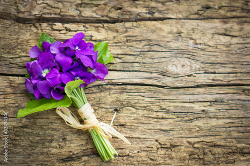 Beautiful bouquet of violets on the wooden background Poster