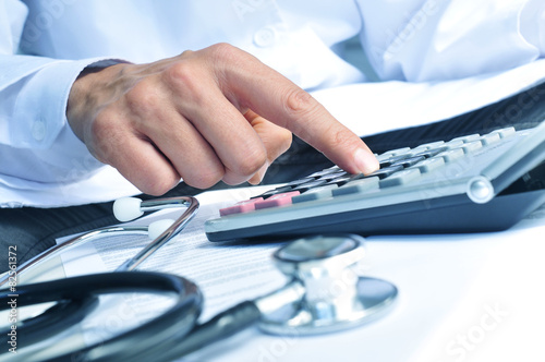 healthcare professional calculating on an electronic calculator Poster