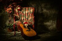 Vintage Acoustic Guitar Leaning Against Antique Chair