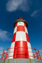 Looking Up At Tall Red And White Lighthouse