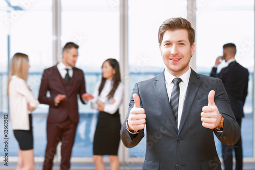 Fototapety, obrazy: Young business man standing in front of his co-workers  talking