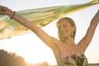 Junge Frau im Sommerkleid hält Tuch in den Wind
