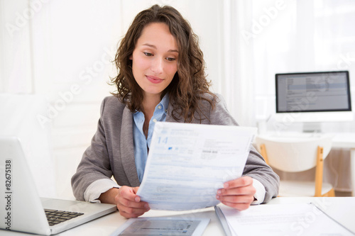 Photo  Young attractive woman doing paperwork
