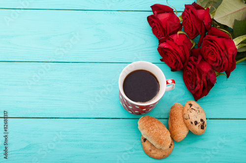 Fotografie, Tablou  Cup of coffee,cruissants and roses on blue wooden background
