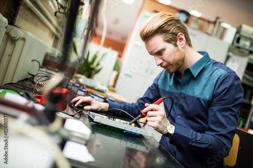 Fotografie, Obraz  Young man in electronics workshop