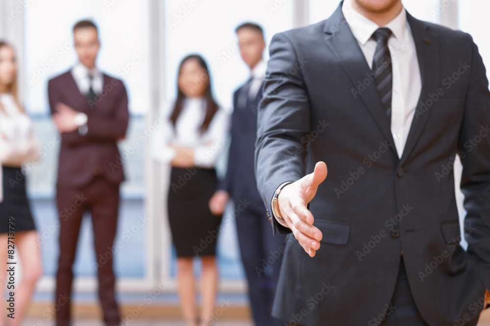 Fototapeta Young business man standing in front of his co-workers  talking