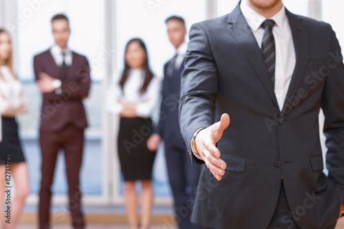 Photo  Young business man standing in front of his co-workers  talking