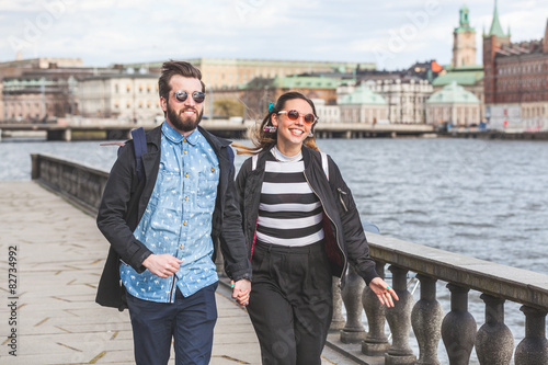 Photo  Young hipster couple running hand in hand in Stockholm