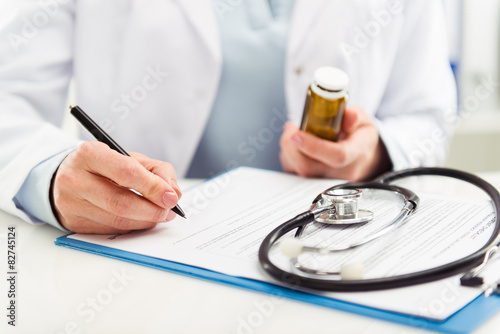 Photo Female doctor filling medical form holding medicine bottle