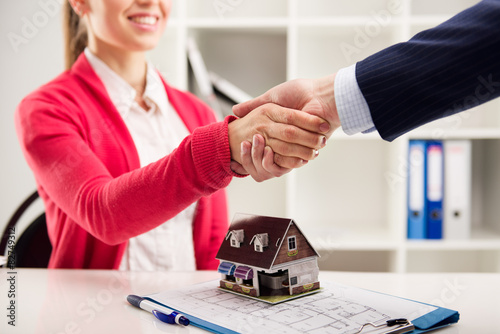 Photo  Business partnership. House agent greeting customer in office