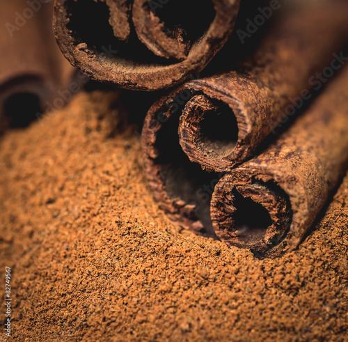Fototapeta Cinnamon sticks with cinnamon powder on wooden background obraz