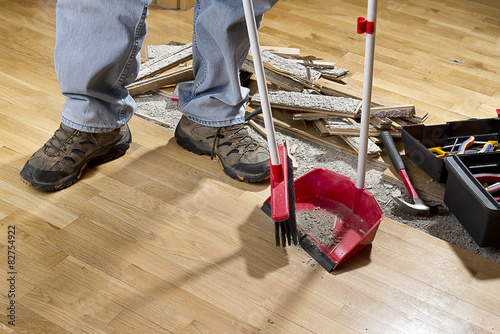 An unrecognizable person with a broom sweeping floor. Wallpaper Mural