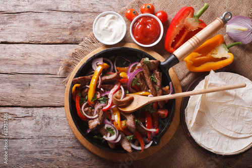 Fotografering  Mexican fajitas on a table. horizontal top view