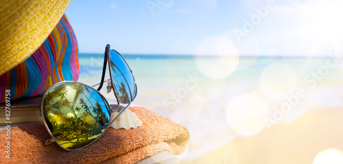 Photo  Straw hat, bag and sun glasses  on a tropical beach