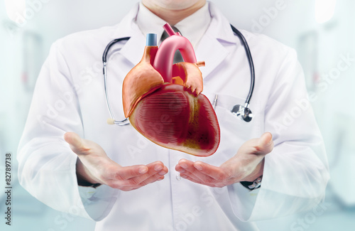 Photo Doctor with stethoscope and heart on the  hands in a hospital