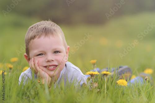 Foto auf Gartenposter Blumenhändler Kind ligt lekker gelukkig in het gras tussen de bloemen