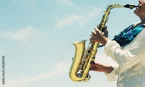 Obraz na płótnie Saxophonist playing on saxophone on blue sky background